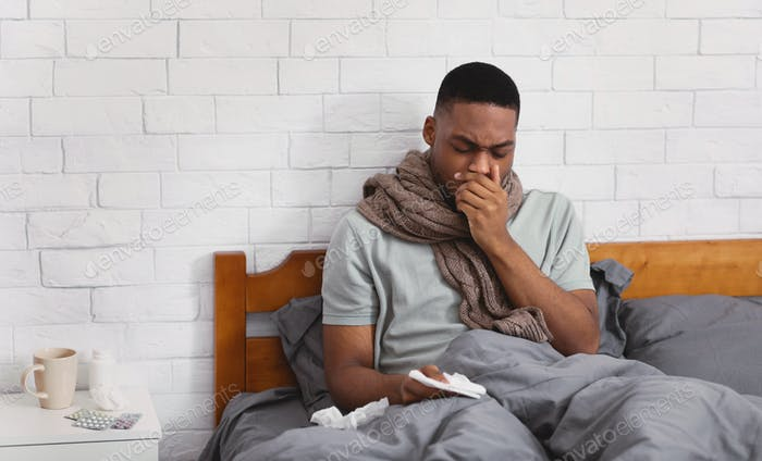 Sick Black Man Coughing Suffering Pneumonia Sitting In Bed Indoors