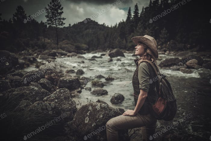 Beautiful woman hiker near wild mountain river.