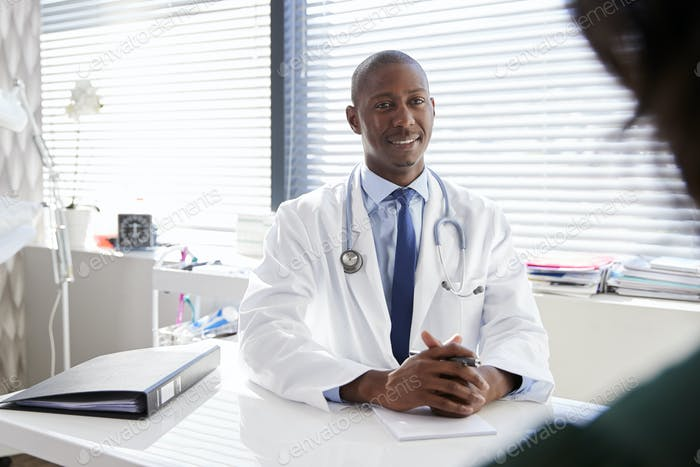 Female Patient In Consultation With Doctor Sitting At Desk In Office