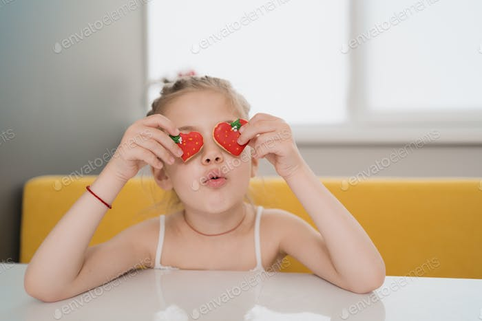 Lovely kid holdig biscuits over eyes