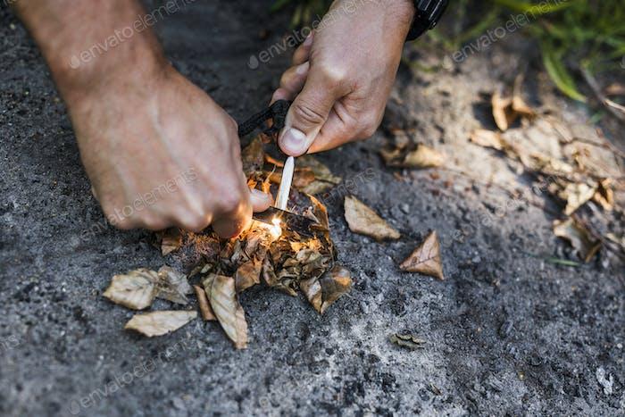 Mann zündet Lagerfeuer
