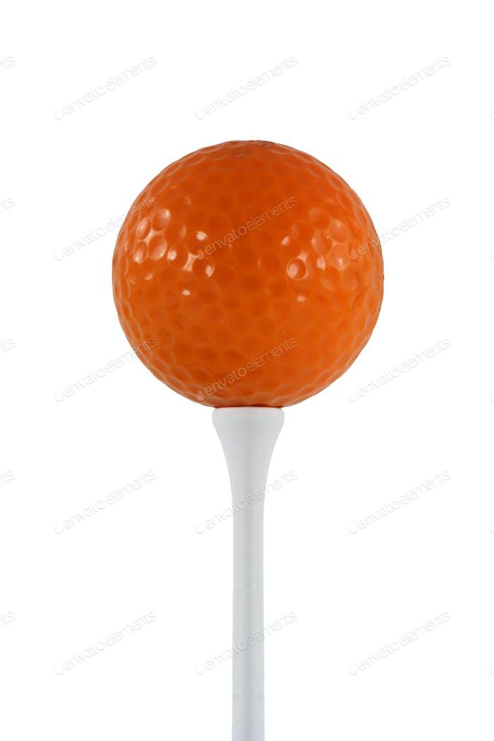 Isolated orange golf ball on a white tee
