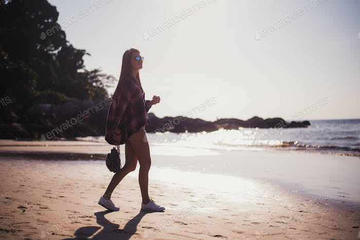Young beautiful girl in stylish sunglasses and with a fashionable bag at sunset walking on a beach