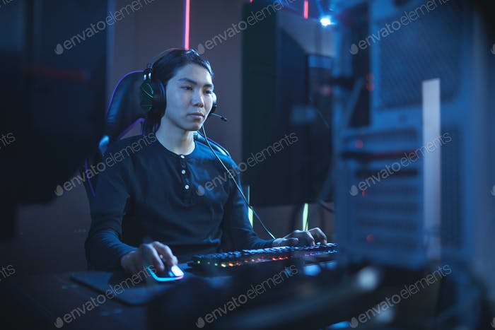 Asian Man Playing Videogames in Computer Club