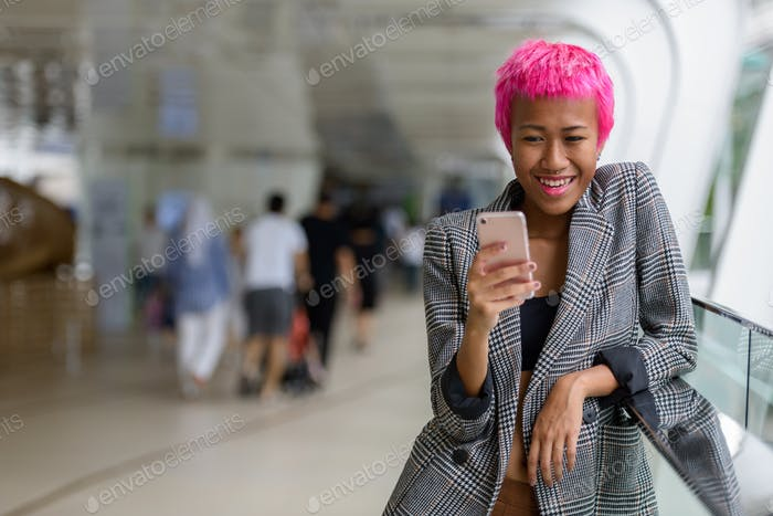 Happy young rebellious Asian businesswoman with pink hair using phone in the city