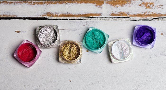Set of sparkling different color nail glitter in jars on the rustic white wooden table