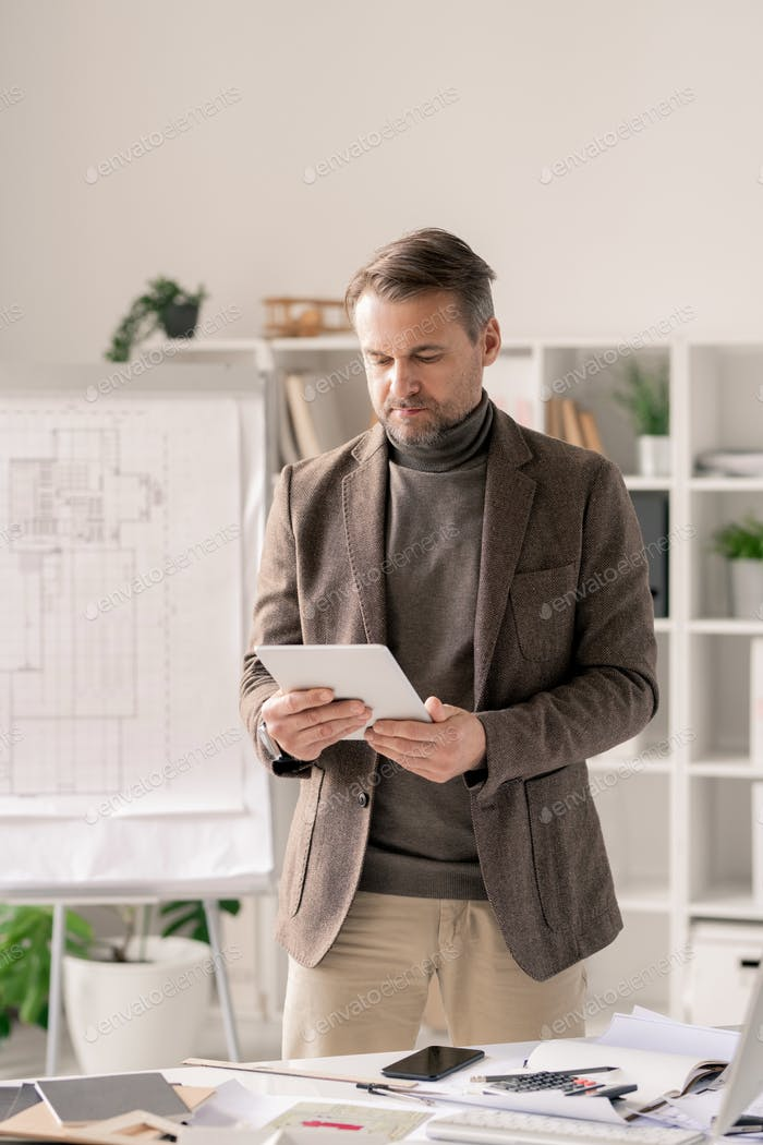Confident architect in formalwear scrolling in tablet while standing by desk