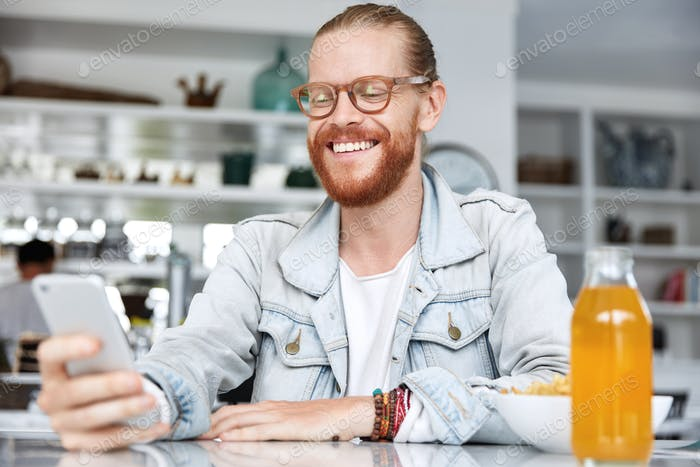 People, fashion, style and communication concept. Smiling pleased fashionable male wears spectacles,
