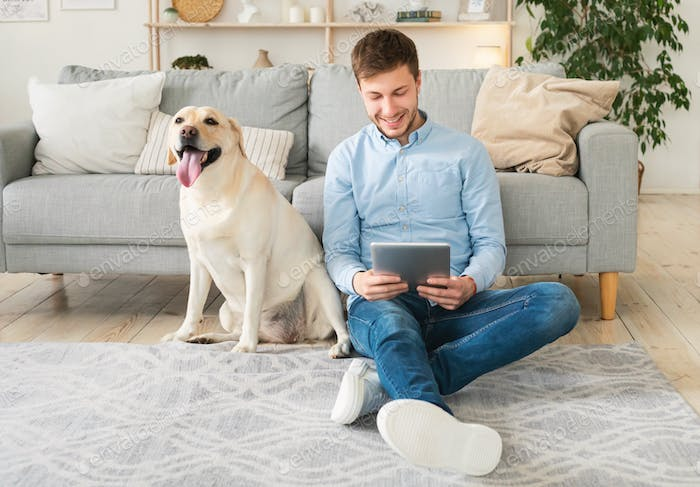 Young man at home with a tablet and dog