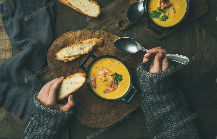 Woman in sweater eating corn soup with prawns, top view