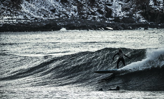 A young man surfing on the ocean, riding a wave with a rocky shoreline.