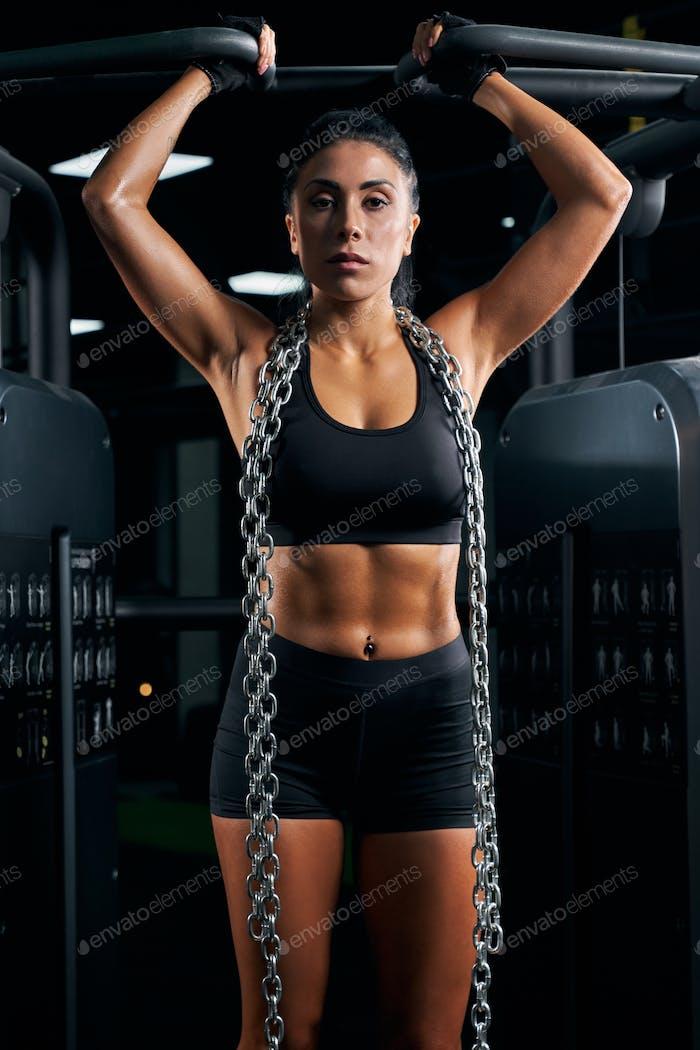 Weibliche Bodybuilder posiert mit Ketten am Hals