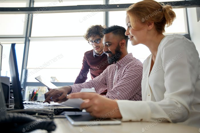 business team with laptop and coffee in office
