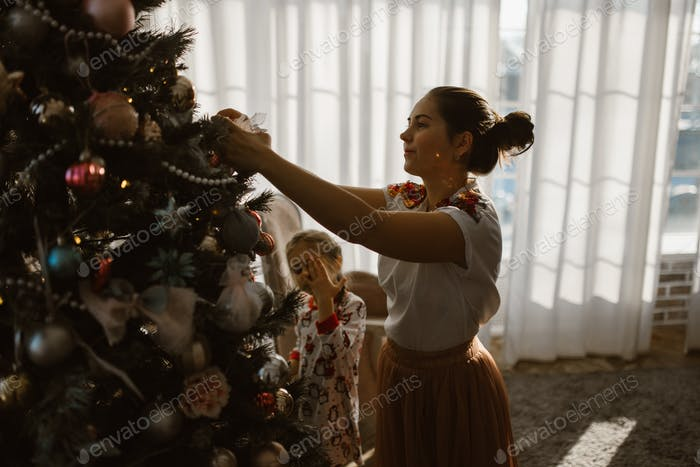 Young mother with two little daughters in pajamas decorate a New Year's tree in the cozy room