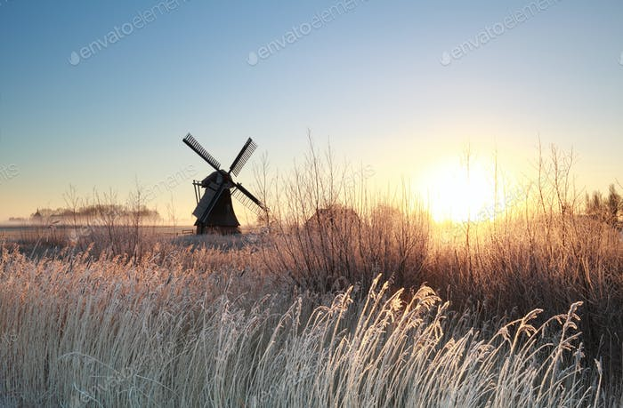 sunrise over Dutch windmill on frosty morning