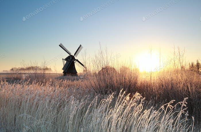 sunrise over Dutch windmill on frosty morning