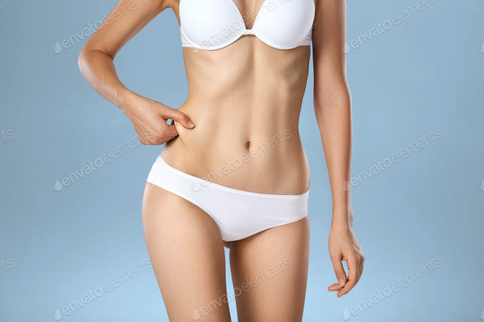 Unrecognizable woman in underwear testing fat layer on waist