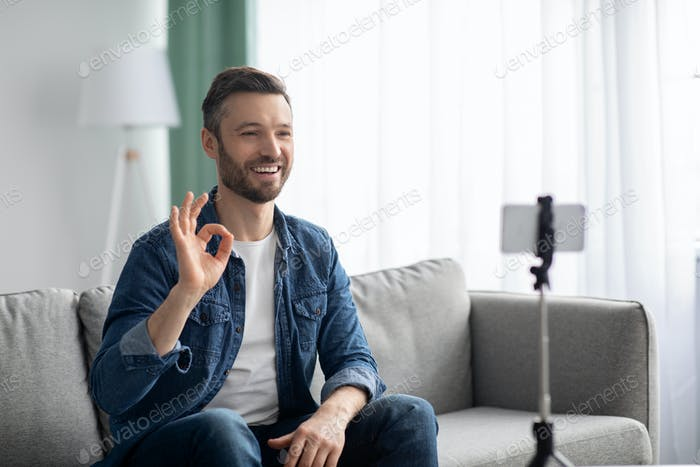 Cheerful middle-aged man blogger broadcasting from home