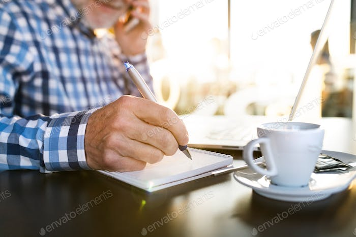 Unrecognizable senior man with smartphone and laptop in cafe