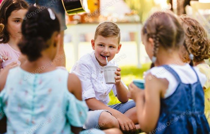 Small children sitting on ground outdoors in garden in summer, drinking.