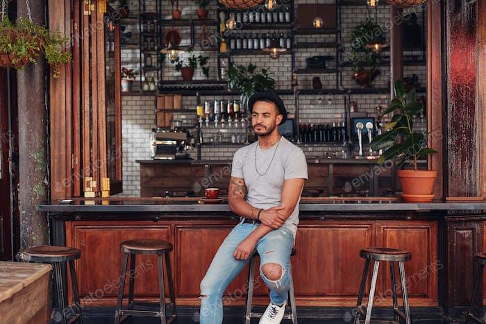 Molestar Hombre sentado solo en un mostrador de café