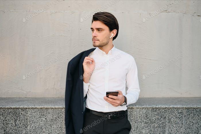 Young man in white shirt with jacket on shoulder using earphones and cellphone over gray wall