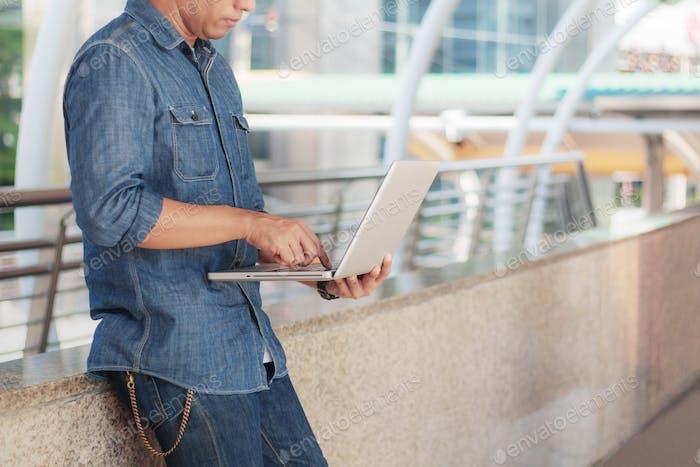 Junger Mann hält Notebook arbeiten