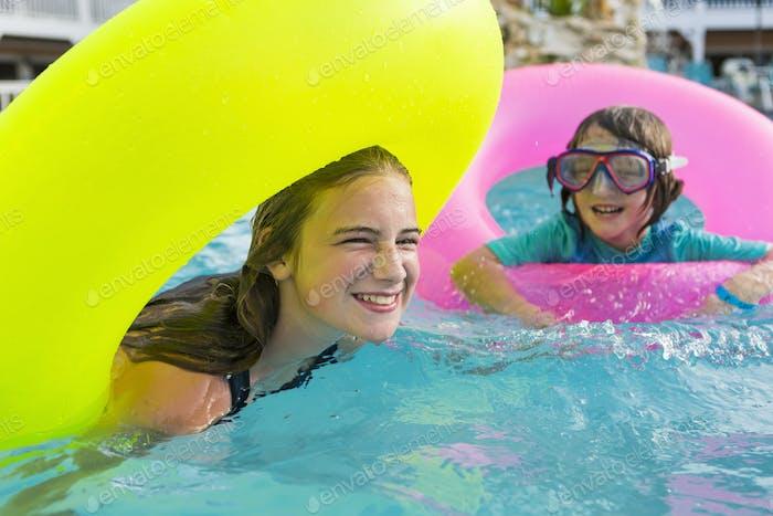 Geschwister spielen im Pool mit bunten Floaties.