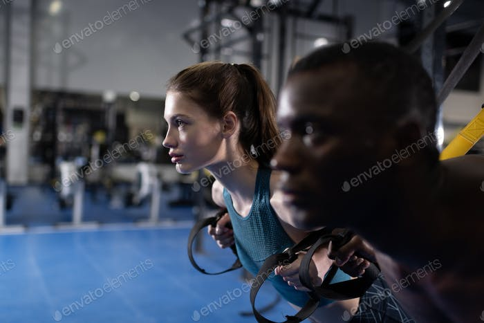 Multiracial couple working out with TRX straps