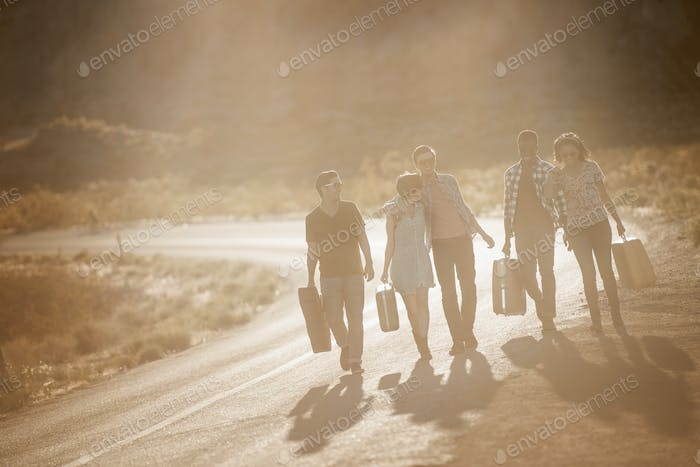 A group of people, men and women, on the road with cases, in open country in the desert.
