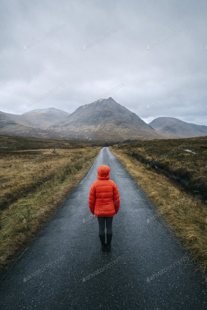 Woman walking on a road in Glen Etive, Scotland