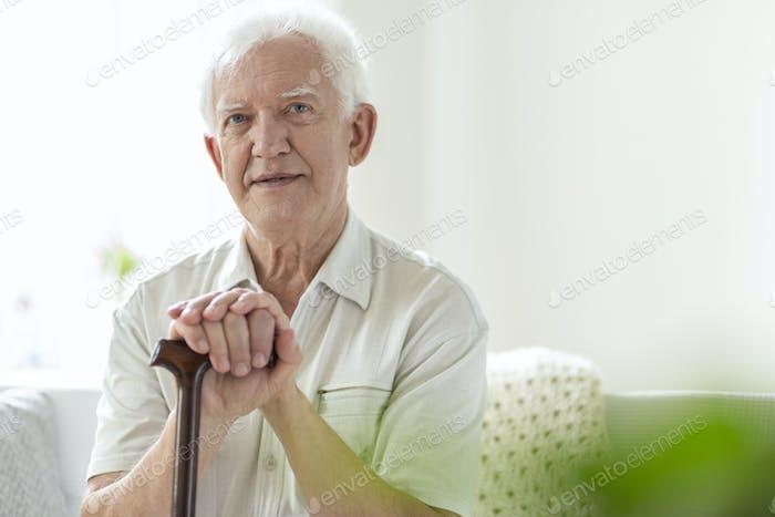 Elderly man with wooden walking stick in the nursing house