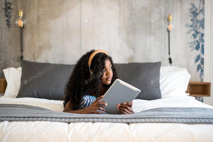 Black girl using tablet in bed