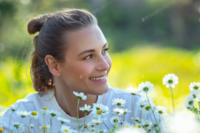 Glückliche junge Frau auf Blumenfeld