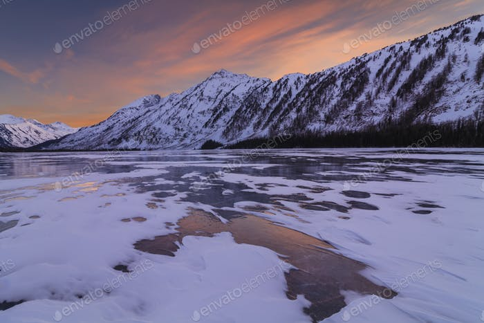 Landschaftlich reizvolle Winterlandschaft mit Bergen und eisigem See