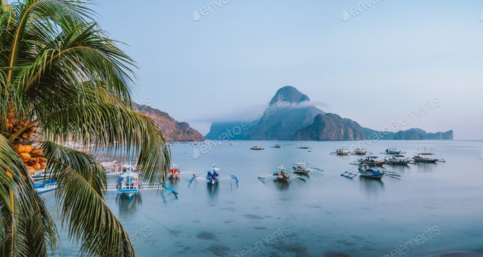 Panoramic scene of trip tourist boats in El Nido at evening sunset light. Palawan, Philippines