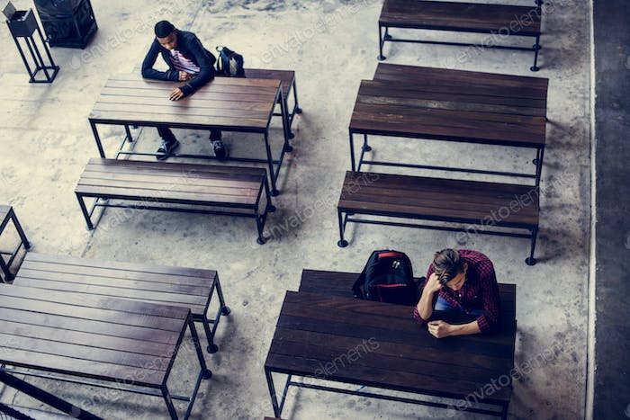 Teenage boys sitting by themselves in an empty canteen