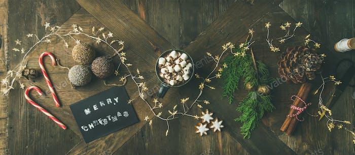Flat-lay of greeting card, glittering toys, mug of hot chocolate,