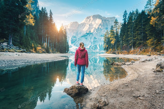 Woman is standing on the coast of Braies lake at sunset