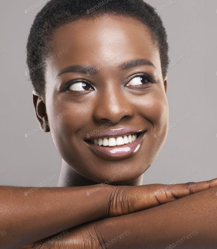 Attraktive afrikanische Frau mit perfekter Haut lächelnd und beiseite schauen