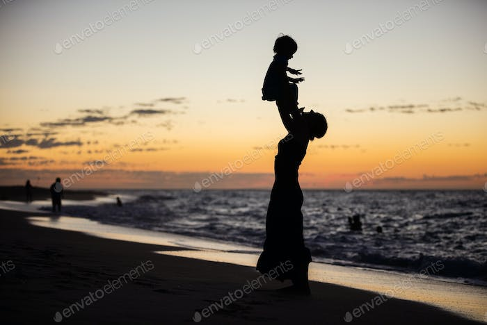 Mother and son having fun on the beach at sunset