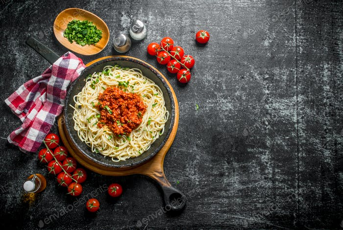 Pasta spaghetti with Bolognese sauce in pan with tomatoes,napkin and chopped greens in bowl.
