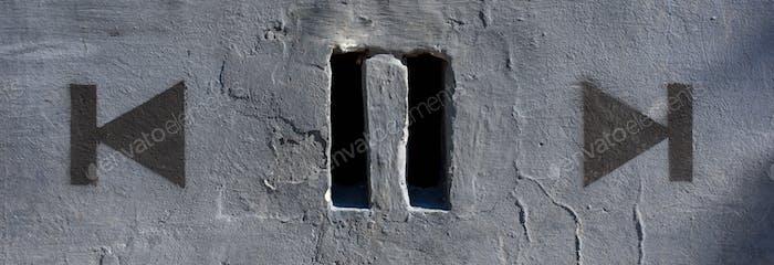 Hin  und her. An der Wand gezeichnet neben zwei Löchern an der Wand, die wie ein Pause-Symbol aussehen.