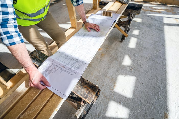 Architect or engineer on construction site looking at blueprints of building house, close up