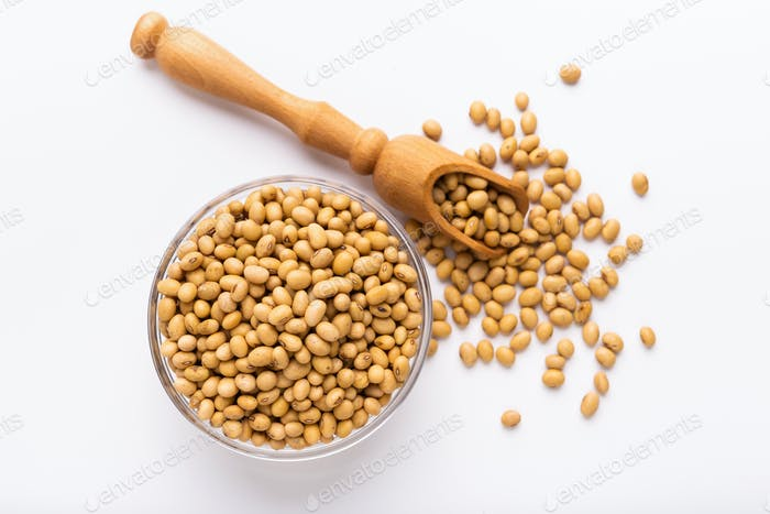 Soya beans in glass bowl and wooden spoon