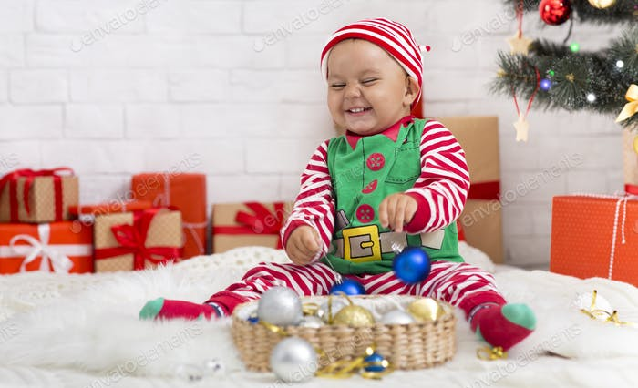 Cheerful baby elf playing with Christmas decorations at home