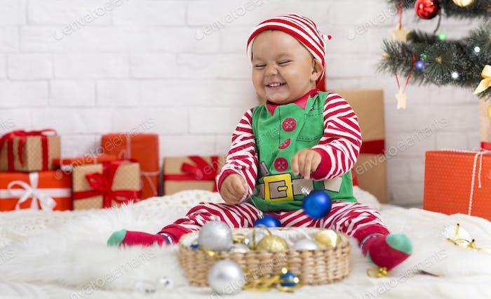 Alegre bebé elfo jugando con decoraciones de Navidad en casa