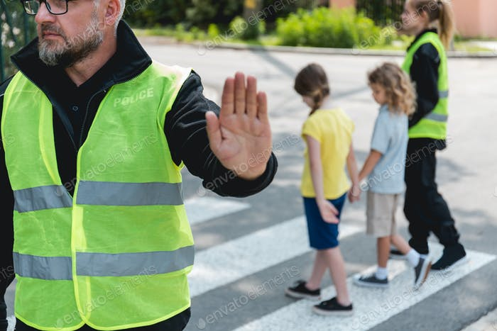 Policeman in a reflective vest raises his hand to stop the car before crossing the street