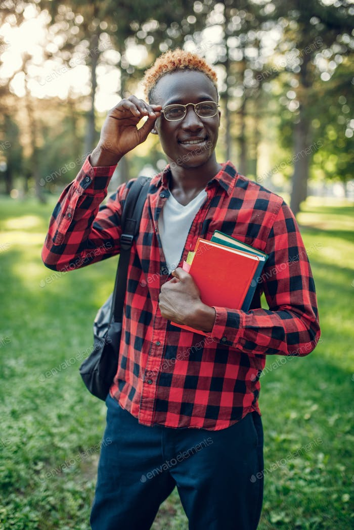 Black student in glasses holds book, summer park