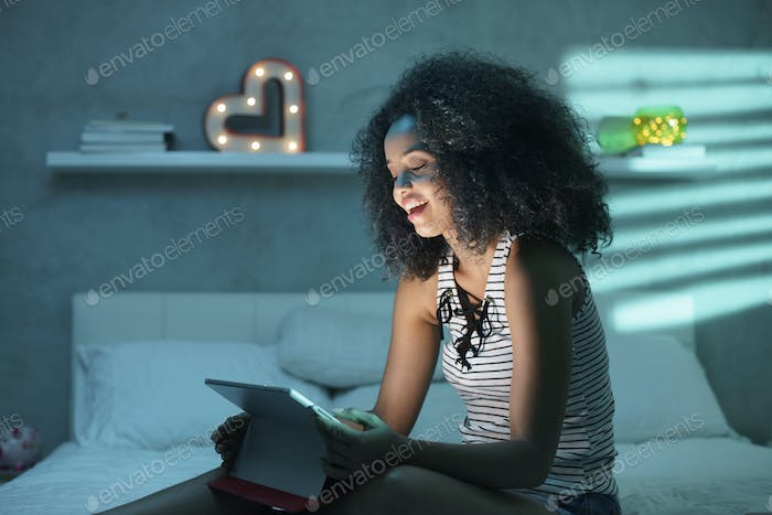 Young Black Woman Watching Movie With Laptop At Night